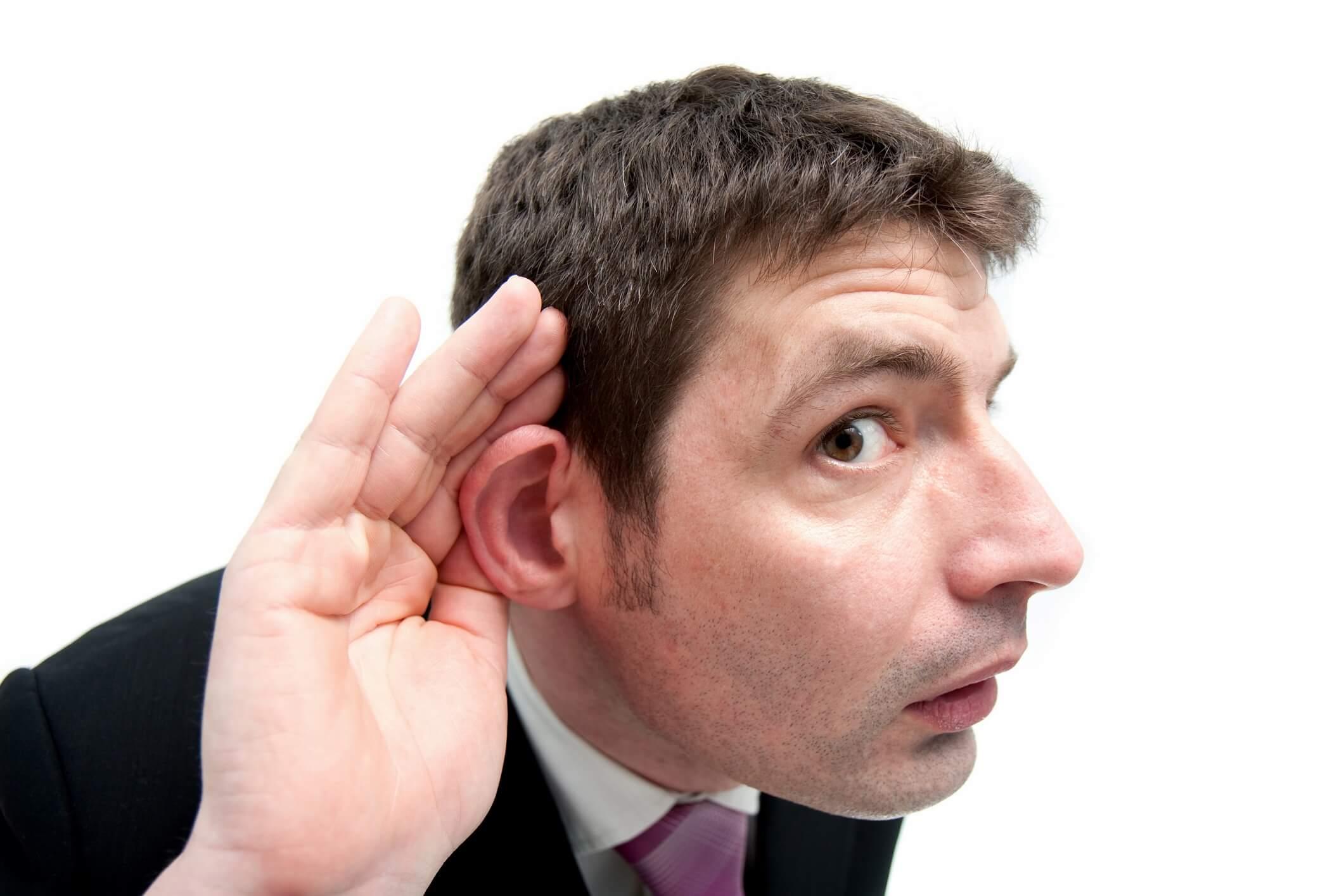 耳に手を当てて聞き返す男性