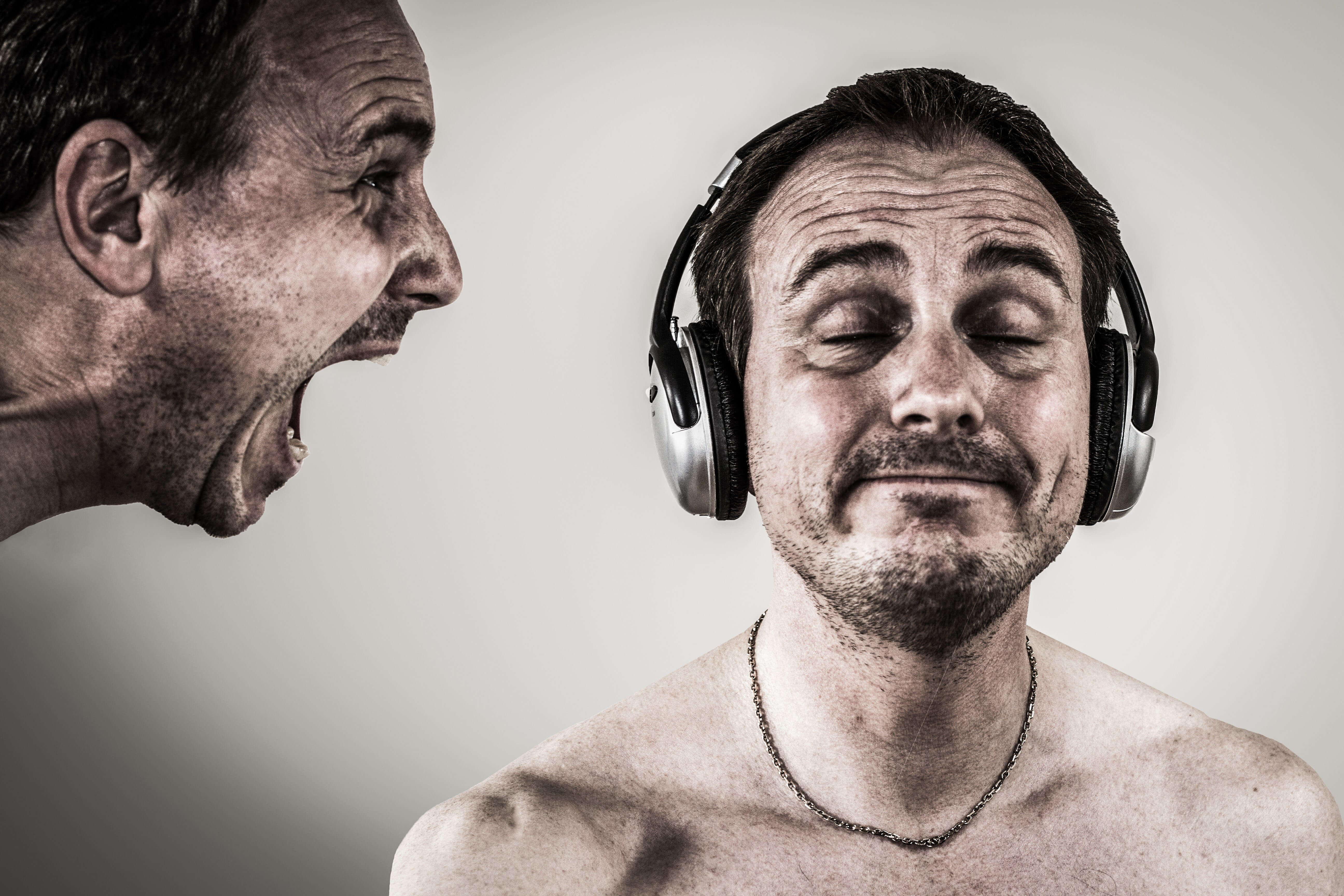 叫ぶ男と、ヘッドホンをしているため聞こえない男