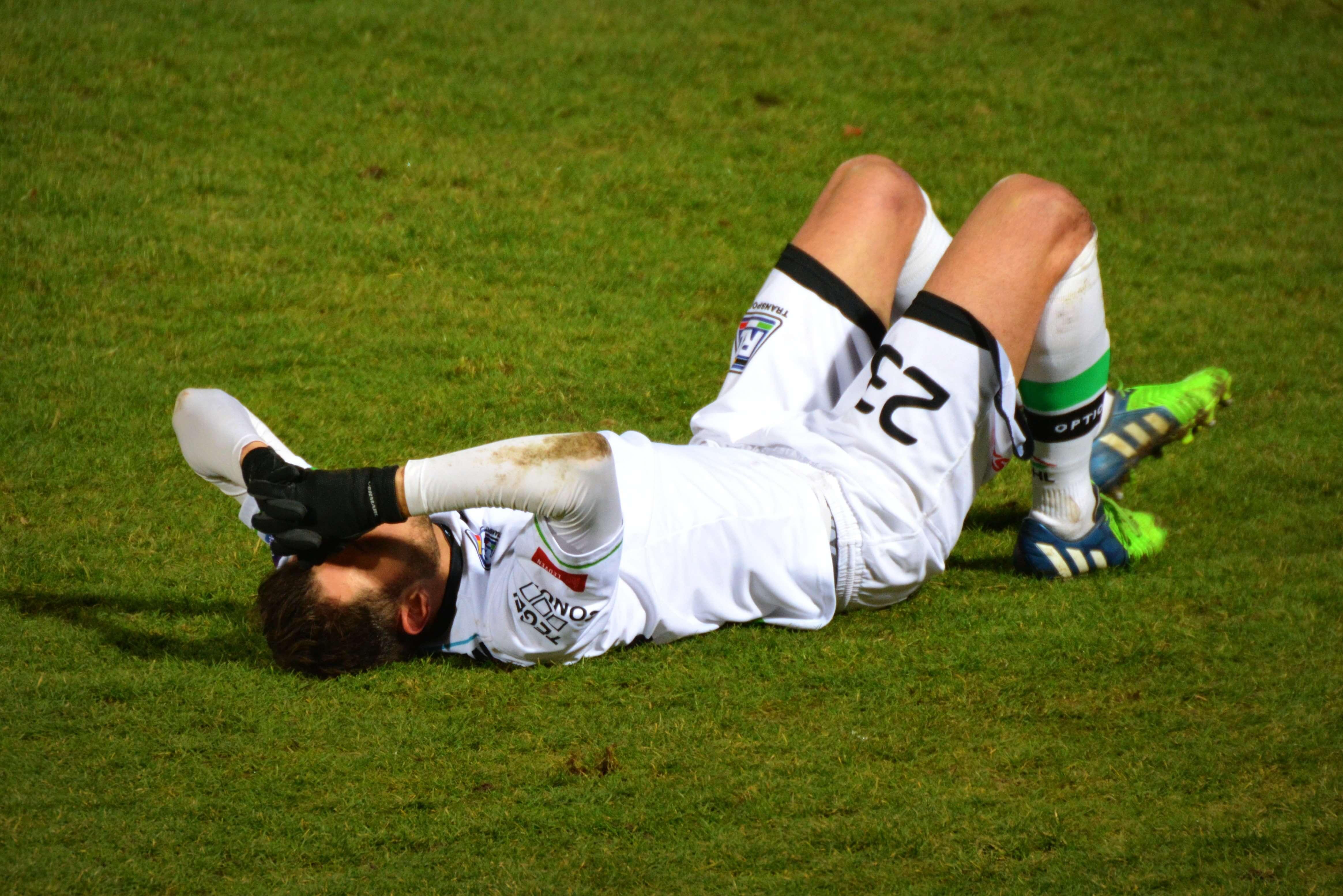 ピッチにで仰向けに寝込むサッカー選手