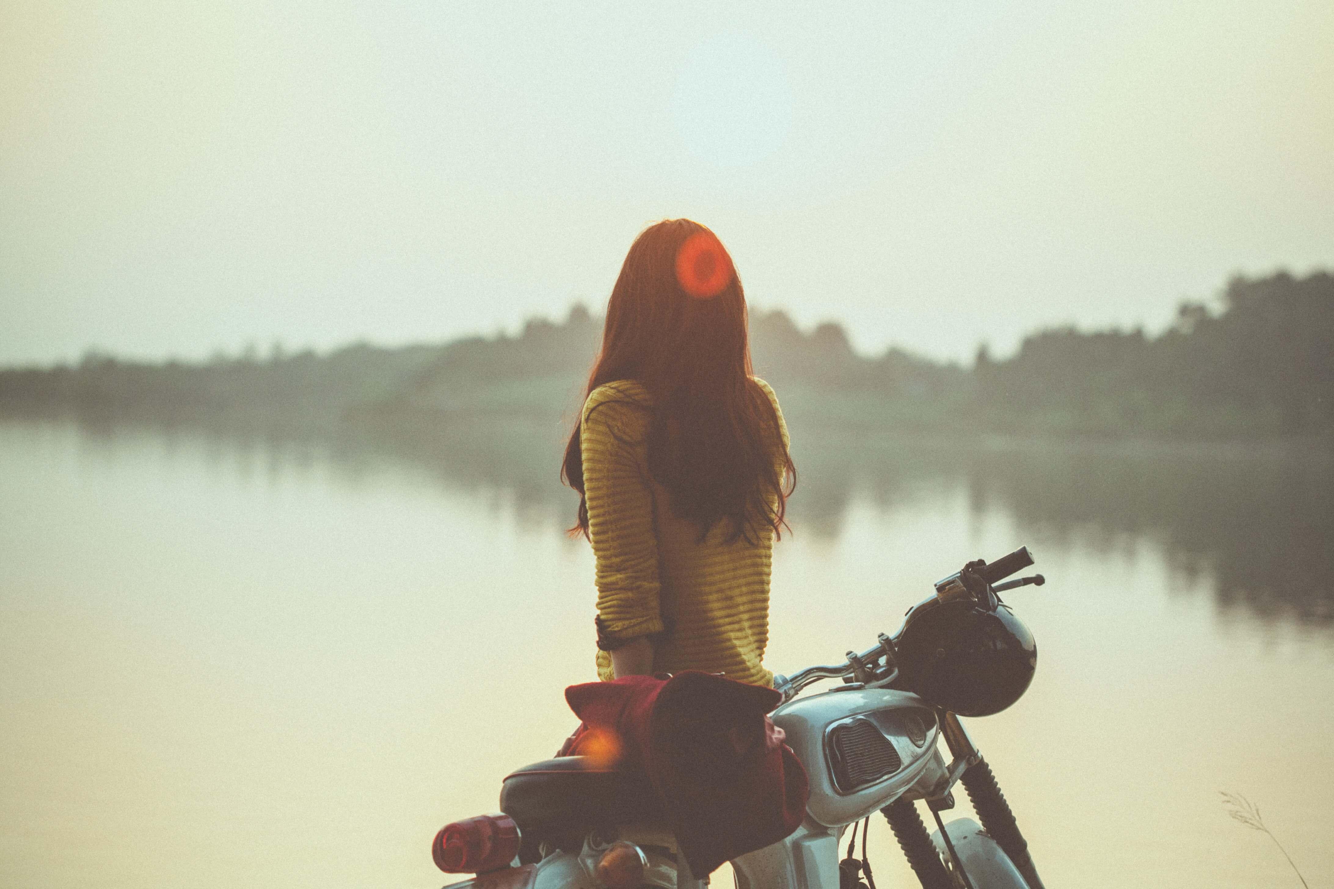 バイクにもたれながら湖を眺める女性