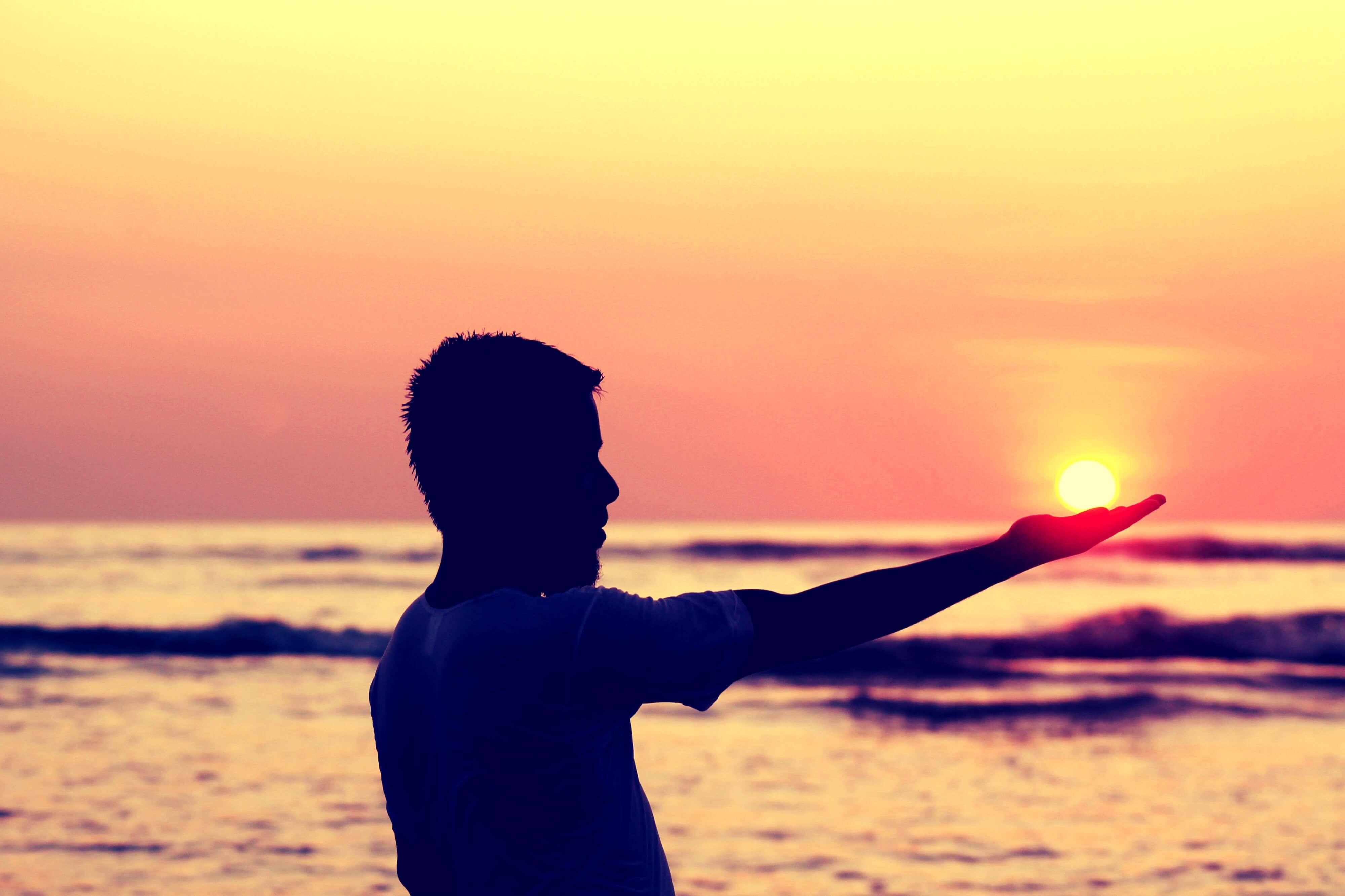 海辺で太陽をのせる男