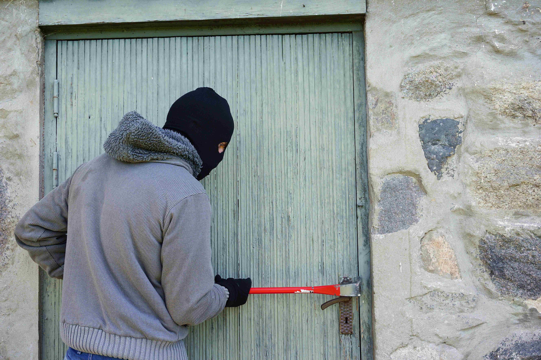 工具でドアをこじ開け進入を試みる強盗